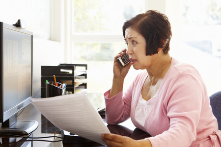bill: Senior Hispanic woman working on computer at home