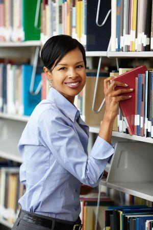 biblioteca: Mujer que trabaja en la biblioteca Foto de archivo