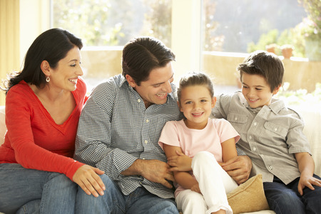 Young Hispanic Family Relaxing On Sofa At Home Banque d'images