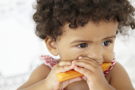 Young Girl Eating Carrot Stick