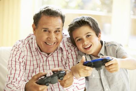 ヒスパニック系の祖父と孫の家庭でビデオ ゲームをプレイ 写真素材