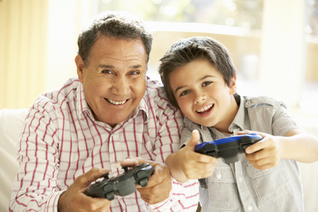 9 year old: Hispanic Grandfather And Grandson Playing Video Game At Home