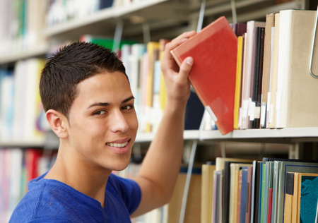 boy 16 year old: Teenage boy working in library