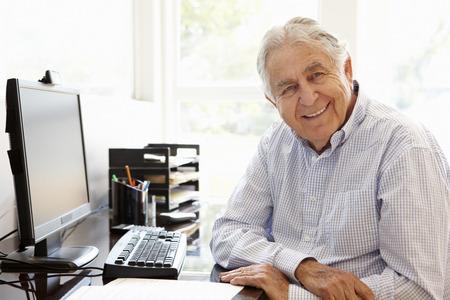 adult 80s: Senior Hispanic man working on computer at home