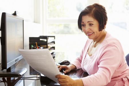 Hogere Spaanse vrouw werkt op de computer thuis