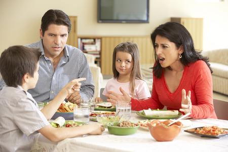 젊은 히스패닉 가족 집에서 식사를 즐기고