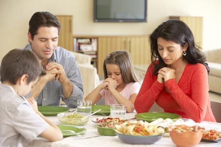 ni�o orando: Familia hisp�nica joven Diciendo rezos Antes de comida en el pa�s