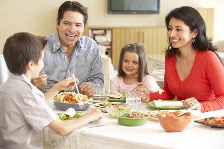 család: Fiatal spanyol család élvezi étkezés otthon