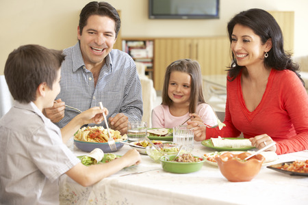 family indoors: Young Hispanic Family Enjoying Meal At Home Stock Photo