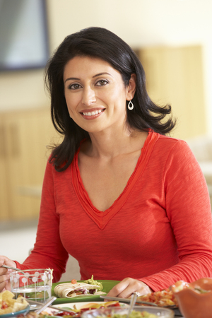 eating dinner: Young Hispanic Woman Enjoying Meal At Home Stock Photo