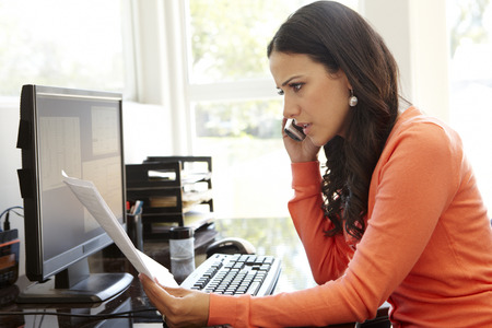 hablando por telefono: Mujer hispánica que trabaja en la oficina en casa