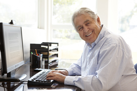 typing man: Senior Hispanic man working on computer at home