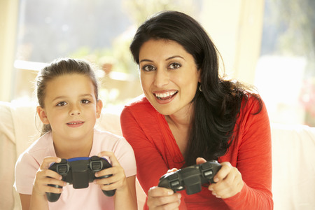 playing video game: Mother And Daughter Playing Video Game At Home