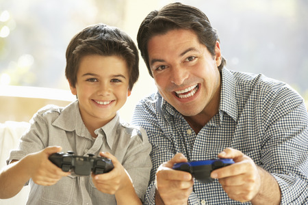 playing video game: Father And Son Playing Video Game At Home