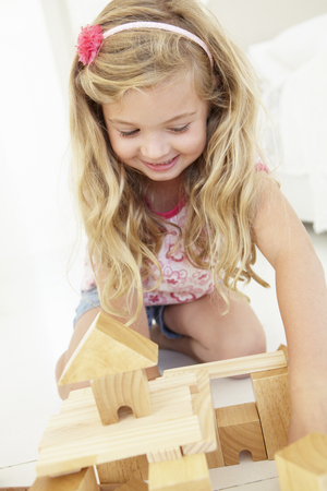 5 year old girl: Young Girl Playing With Wooden Building Blocks In Bedroom