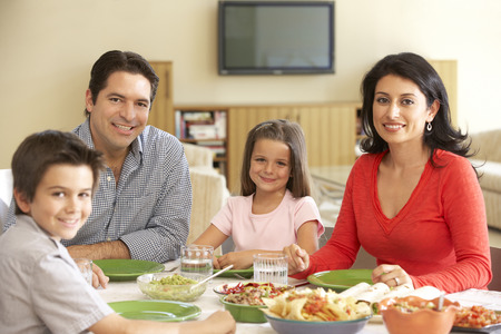 meal: Young Hispanic Family Enjoying Meal At Home Stock Photo