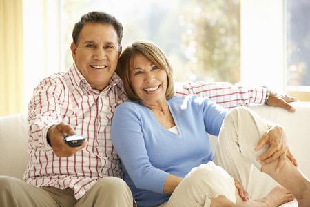 pareja viendo television: Pares hispánicos mayores que ven la TV en Inicio