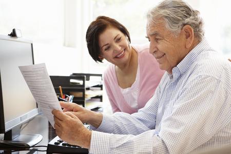 personas trabajando en oficina: Pares hispánicos mayores que trabajan en equipo en casa