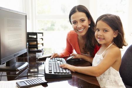 madre trabajando: Hispanic madre e hija usando la computadora en casa Foto de archivo