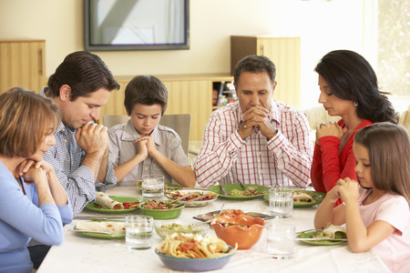 Extended Hispanic Family Saying Prayers Before Meal At Home