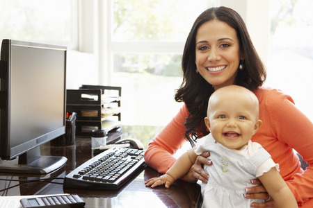 Hispanic mother with baby in working home office