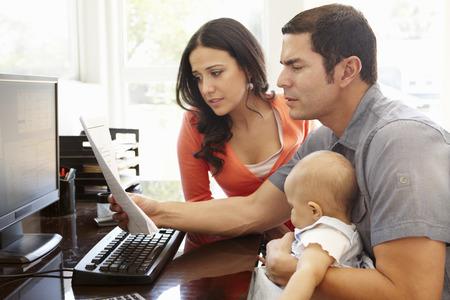 factura: Pareja de hispanos y el bebé en la oficina en casa Foto de archivo