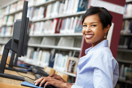 Woman working on computer in library Imagens