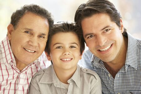 Portrait Of Hispanic Grandfather, Adult Father And Son Relaxing At Home Stock Photo