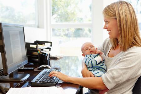 trabajando: Madre que trabaja en la oficina en casa con el bebé