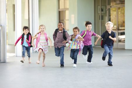 ni�os en la escuela: Grupo de escolares de primaria que se ejecutan afuera