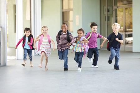 Skupina elementárních věku školáků běžící mimo Reklamní fotografie