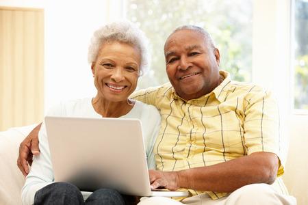 mujeres mayores: Pares mayores usando la computadora portátil afroamericano