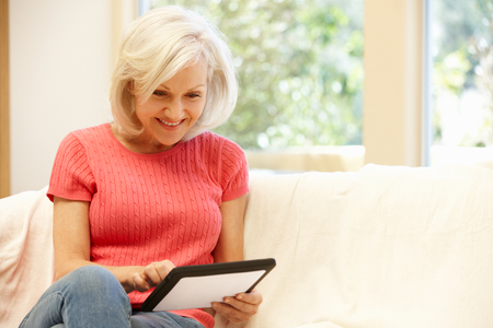 mid age: Mid age woman using tablet at home Stock Photo