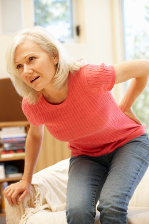 mujeres de espalda: Mujer de mediana edad con dolor de espalda
