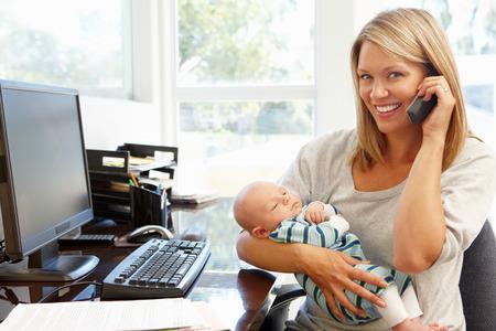 madre trabajando: Madre que trabaja en la oficina en casa con el beb�