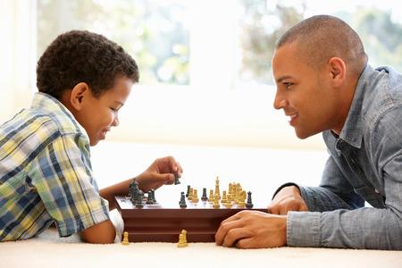jugando ajedrez: Padre jugando al ajedrez con el hijo