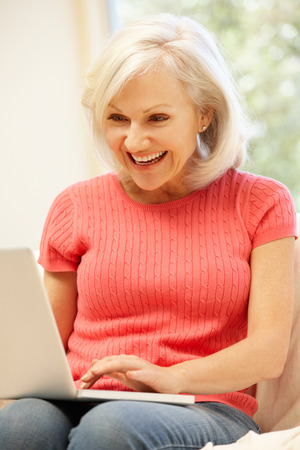 mid age: Mid age woman using laptop at home Stock Photo