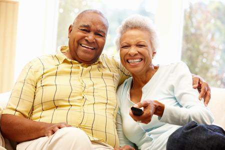 viendo television: Pares afroamericanos viendo la televisi�n Foto de archivo