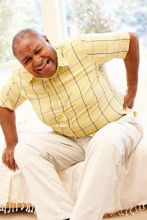 Senior Afro-Amerikaanse man met rugpijn Stockfoto