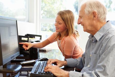 persona mayor: Hombre mayor y su nieta utilizando equipo Foto de archivo