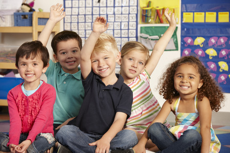 4 5 year old: Group Of Elementary Age Schoolchildren Answering Question In Class