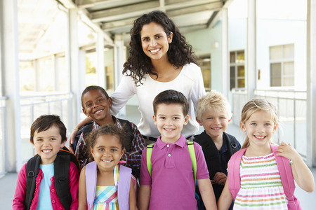 female teacher: Group Of Elementary Age Schoolchildren Standing Outside With Teacher Stock Photo