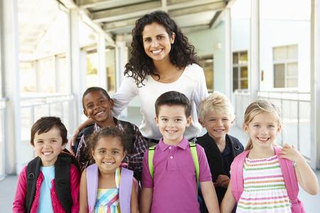 profesor alumno: Grupo de primaria los escolares de pie fuera con el profesor Foto de archivo