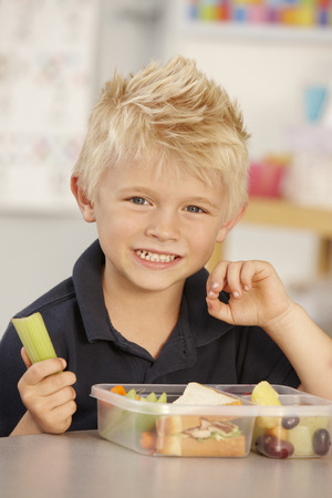 lunch: Elementary Age Schoolboy Eating Healthy Packed Lunch In Class Stock Photo