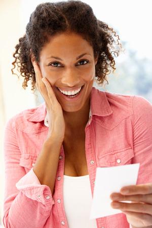 Receiving: Mixed race woman receiving good news Stock Photo