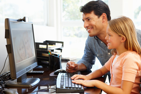 skype: Father and daughter using skype in home office