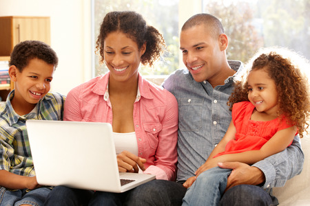 working together: Family working on laptop at home Stock Photo