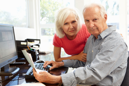 70s adult: Senior man and daughter using computer at home Stock Photo
