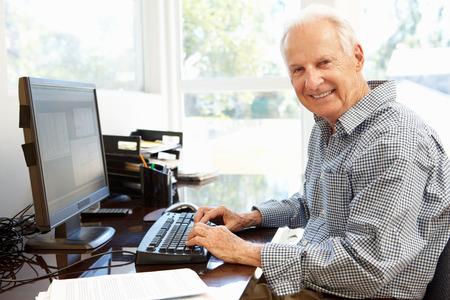 Starší muž pracující na počítači doma