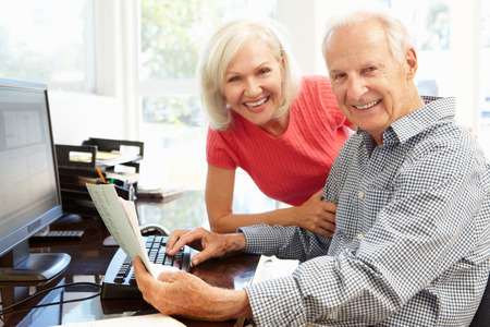 Senior man and daughter using computer at home Stockfoto